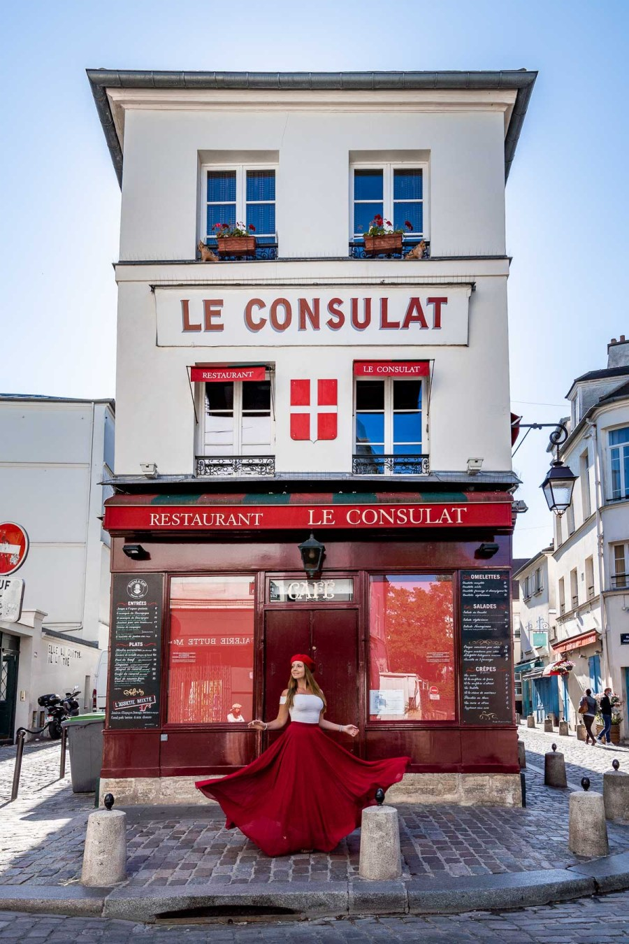 Girl in a red skirt twirling in front of Le Consulat in Montmartre, one of the best Paris Instagram Spots