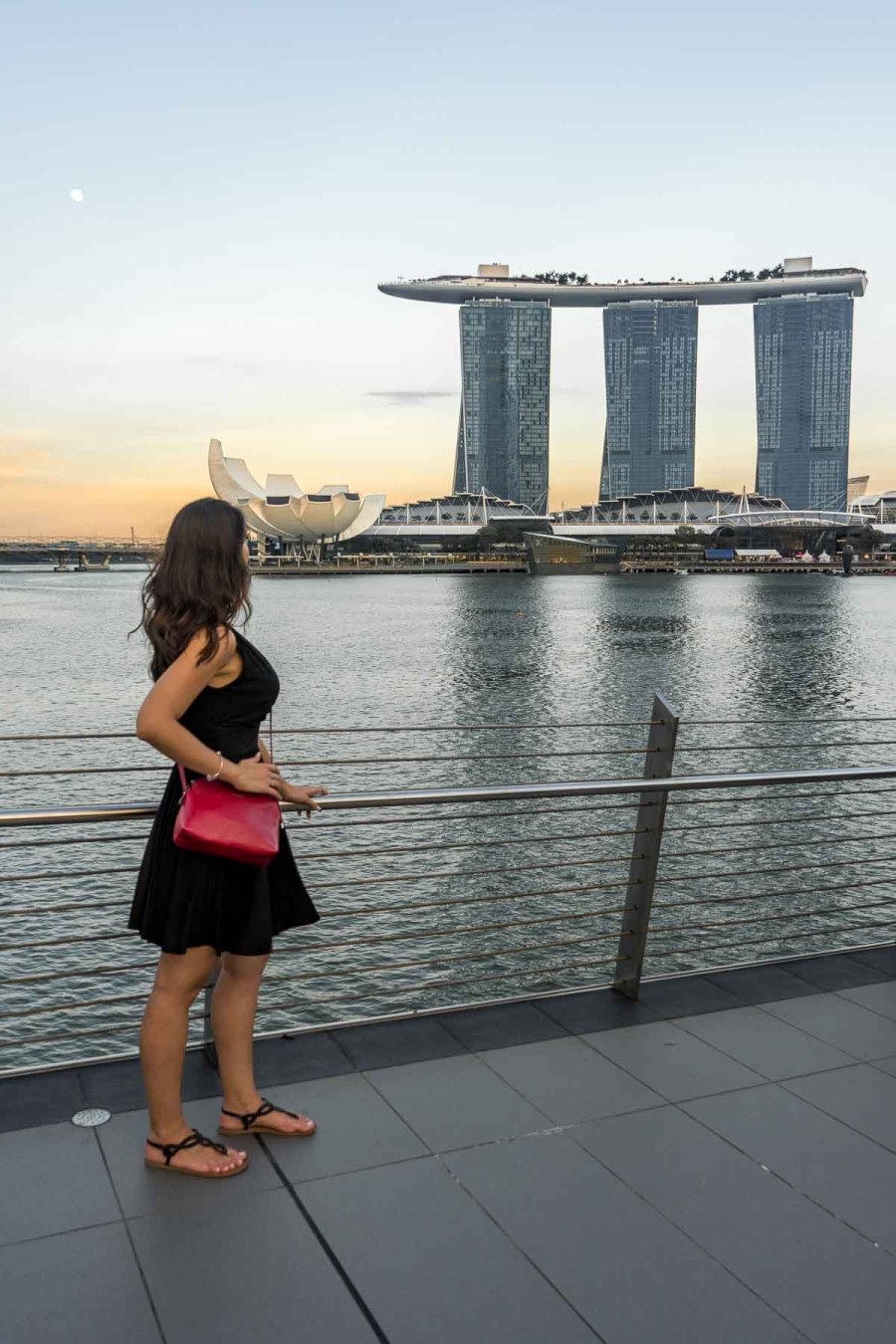 Girl in a black dress watching the sunset over Marina Bay Sands in Singapore
