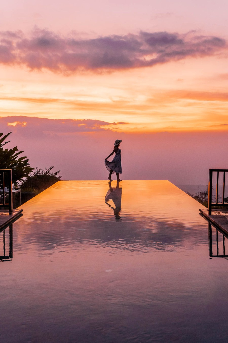 Girl standing on the edge of an infinity pool during sunset at Munduk Moding Plantation