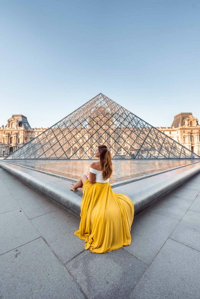 Girl in a yellow skirt sitting in front of one of the pyramids at the Louvre, one of the most instagrammable places in Paris