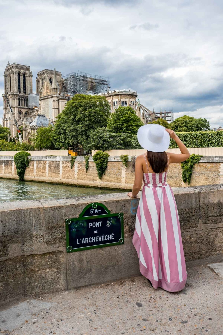 Girl in a pink-white dress standing on Pont L'Archevéche, looking at the Notre Dame in Paris