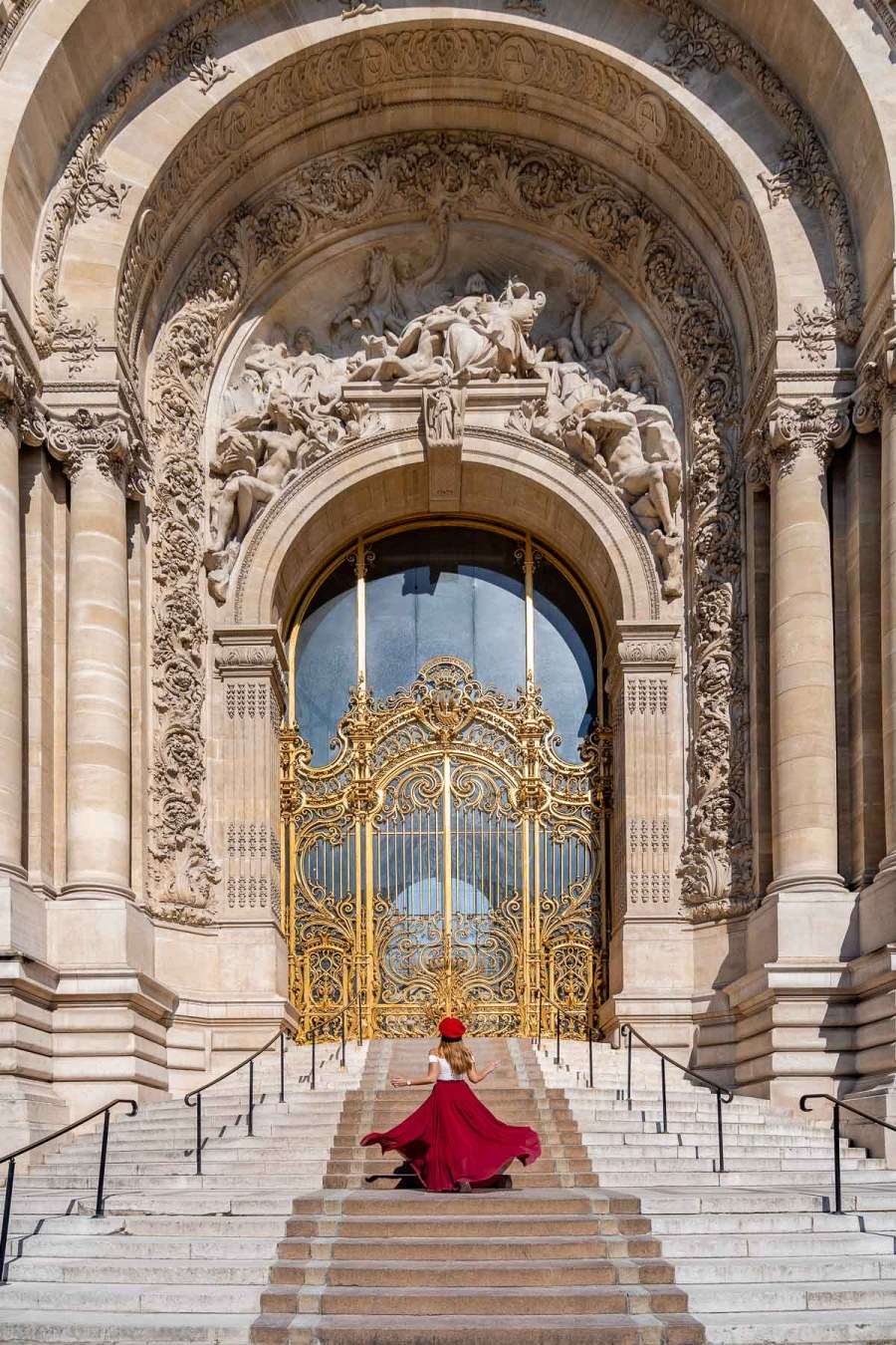 Girl in a red skirt twirling in front of Petit Palais in Paris