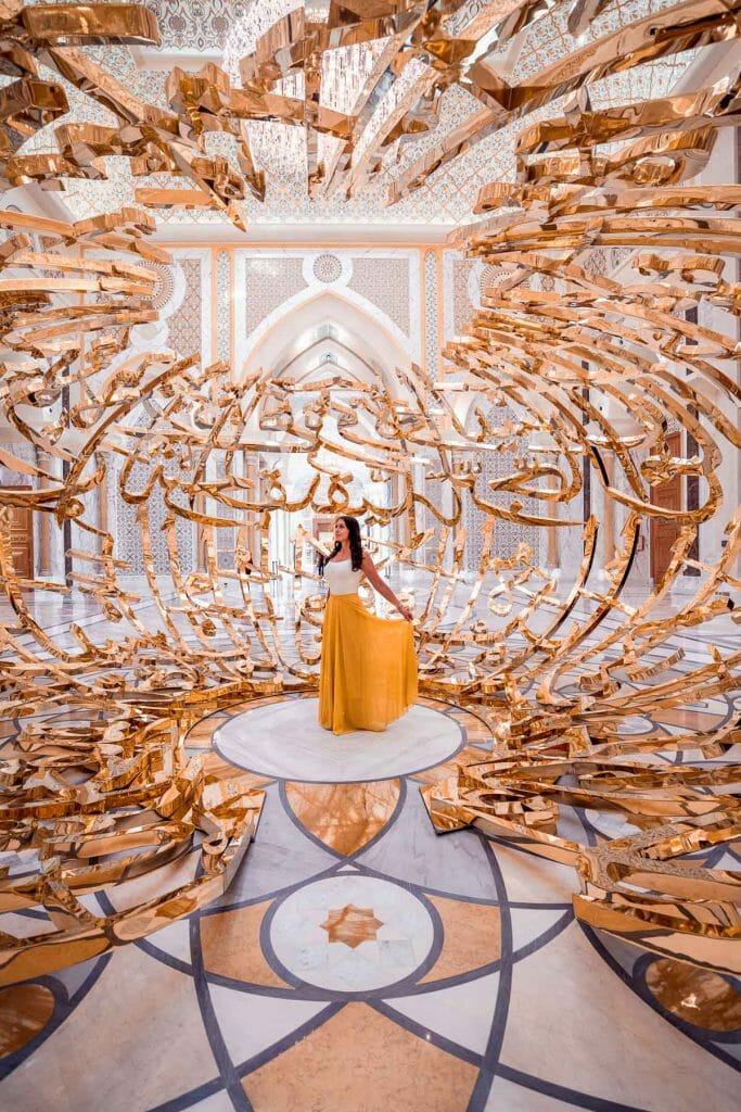 Girl in a yellow skirt standing in the middle of a golden structure in the Qasr Al Watan Palace Abu Dhabi