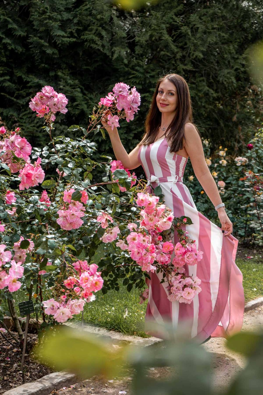 Girl in a pink dress standing in the rose garden at Jardin des Plantes in Paris