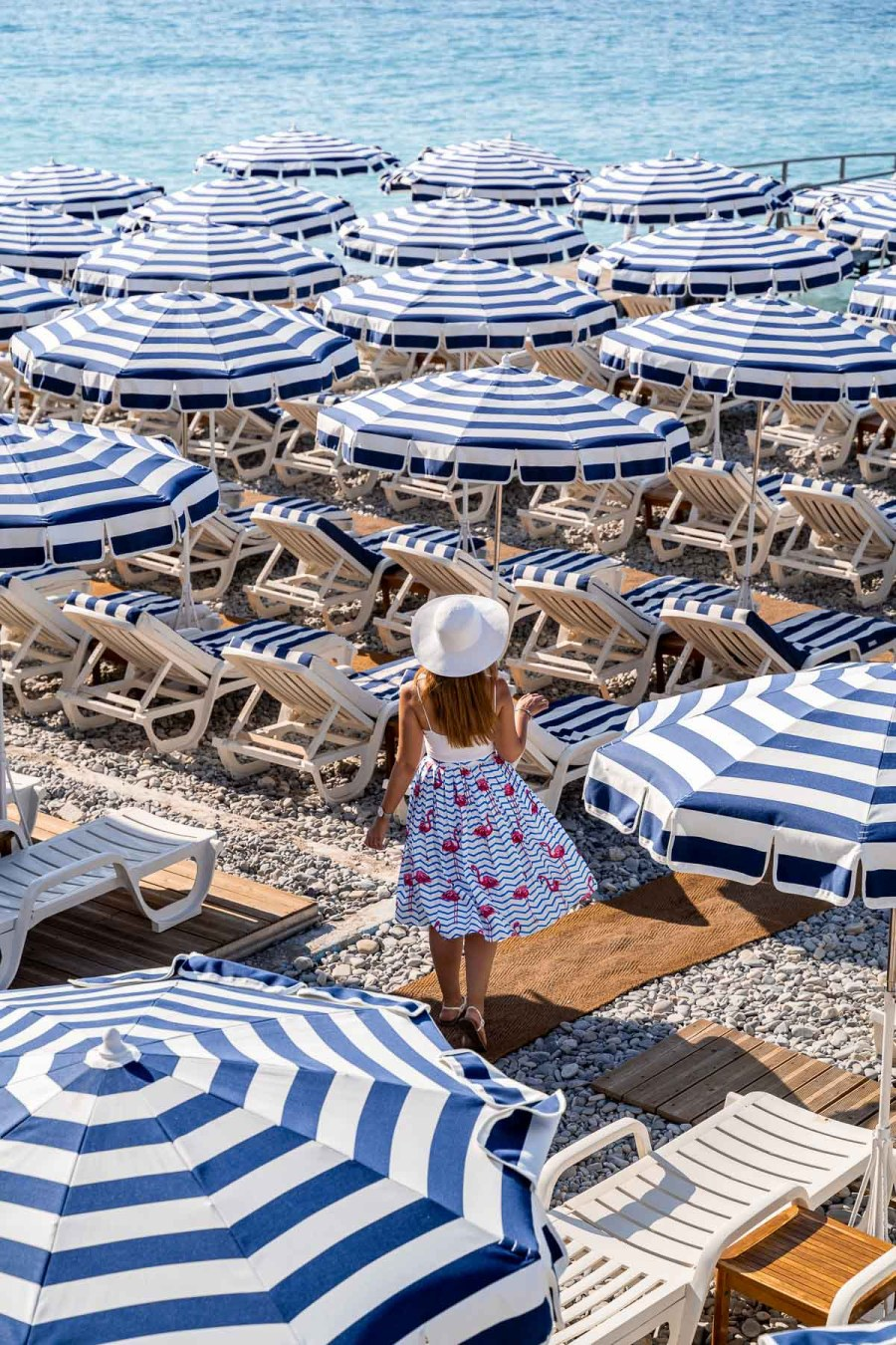 Girl in a flamingo skirt walking between the white-blue parasols at Ruhl Plage in Nice, France
