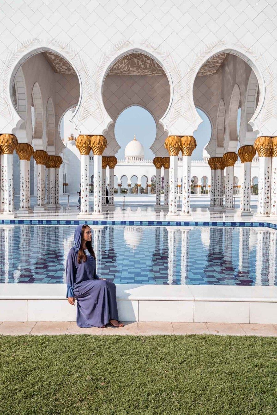 Girl in a blue abaya sitting by the pool at Sheikh Zayed Grand Mosque, Abu Dhabi