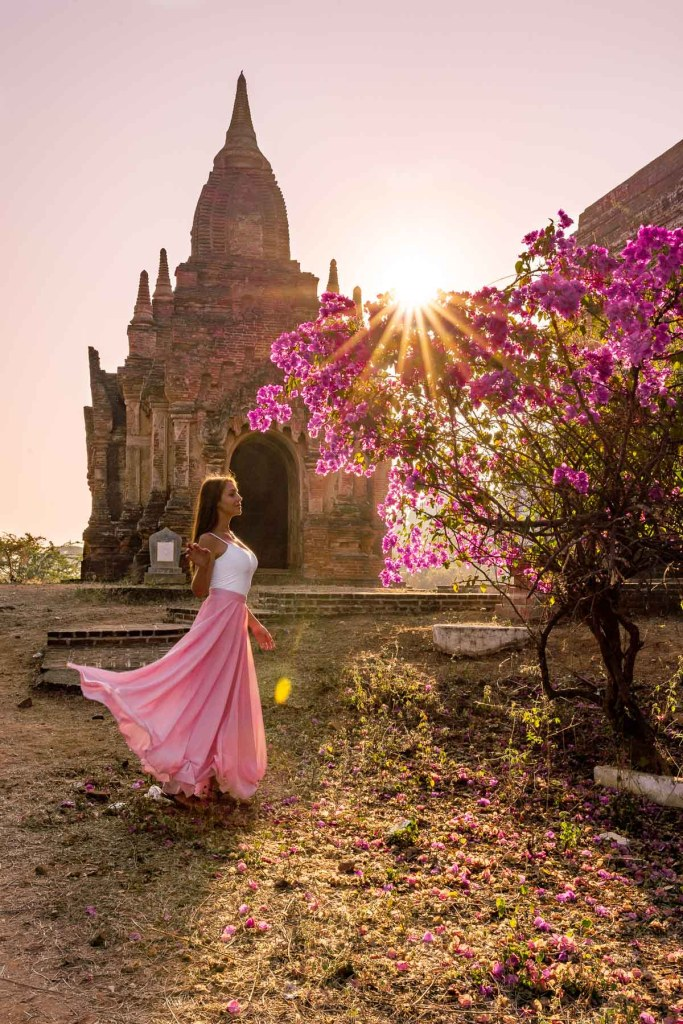 Girl in a pink dress watching the sunrise in front of a pink tree in Bagan, Myanmar