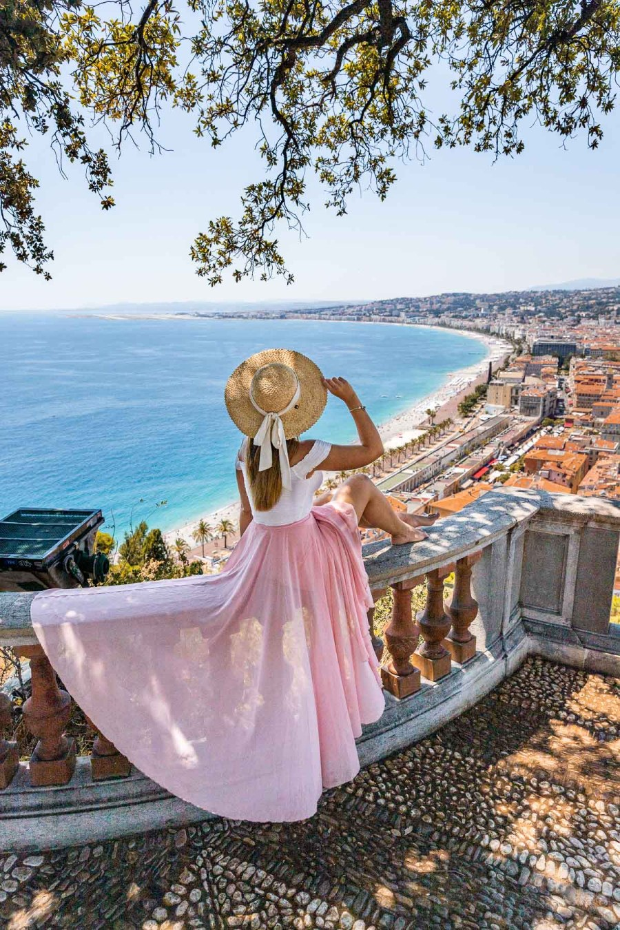 Girl in a pink skirt sitting on the railings at Castle Hill, looking at the panoramic view of Nice