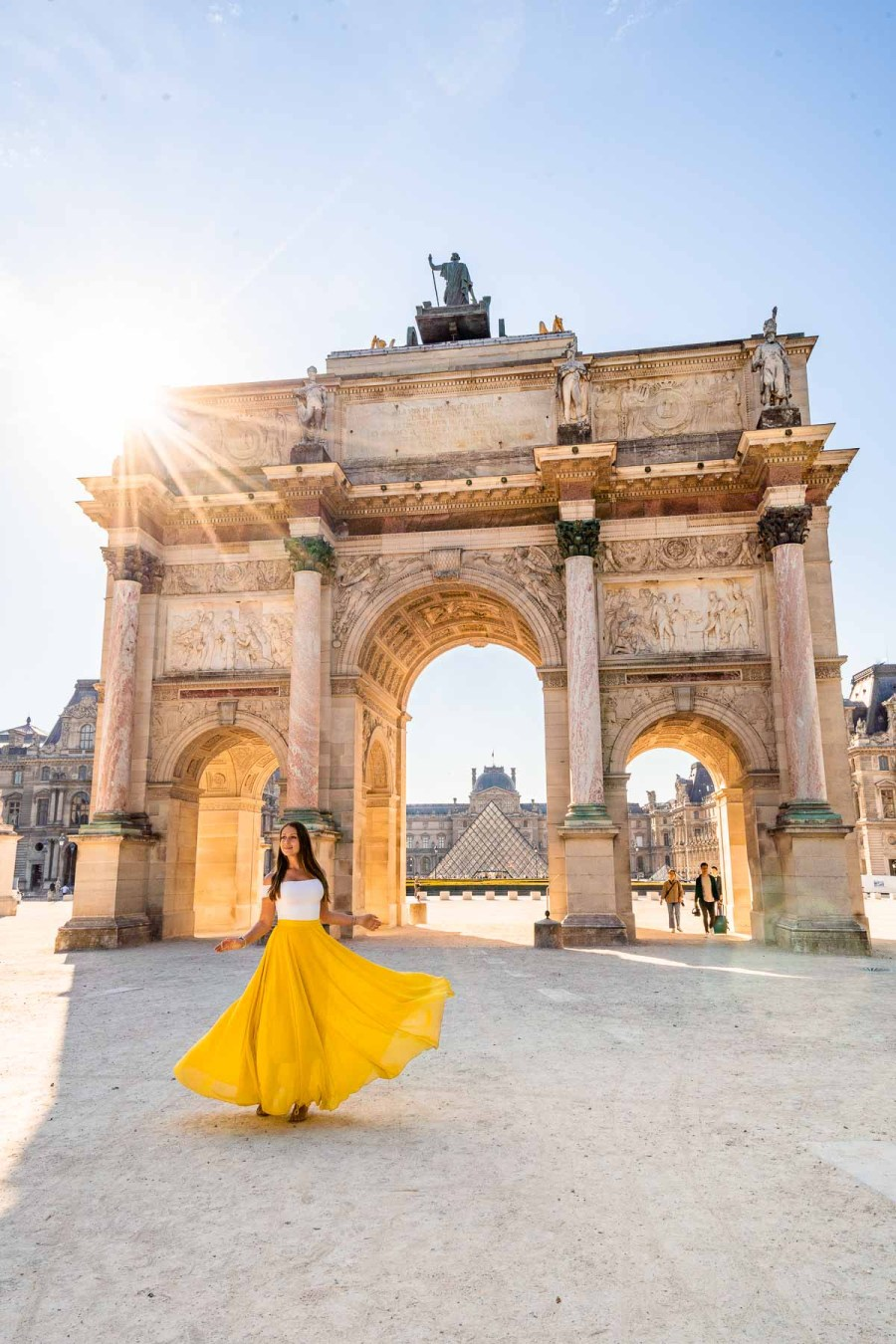 Girl in a yellow skirt twirling in front of Arc de Triomphe du Carrousel in Paris