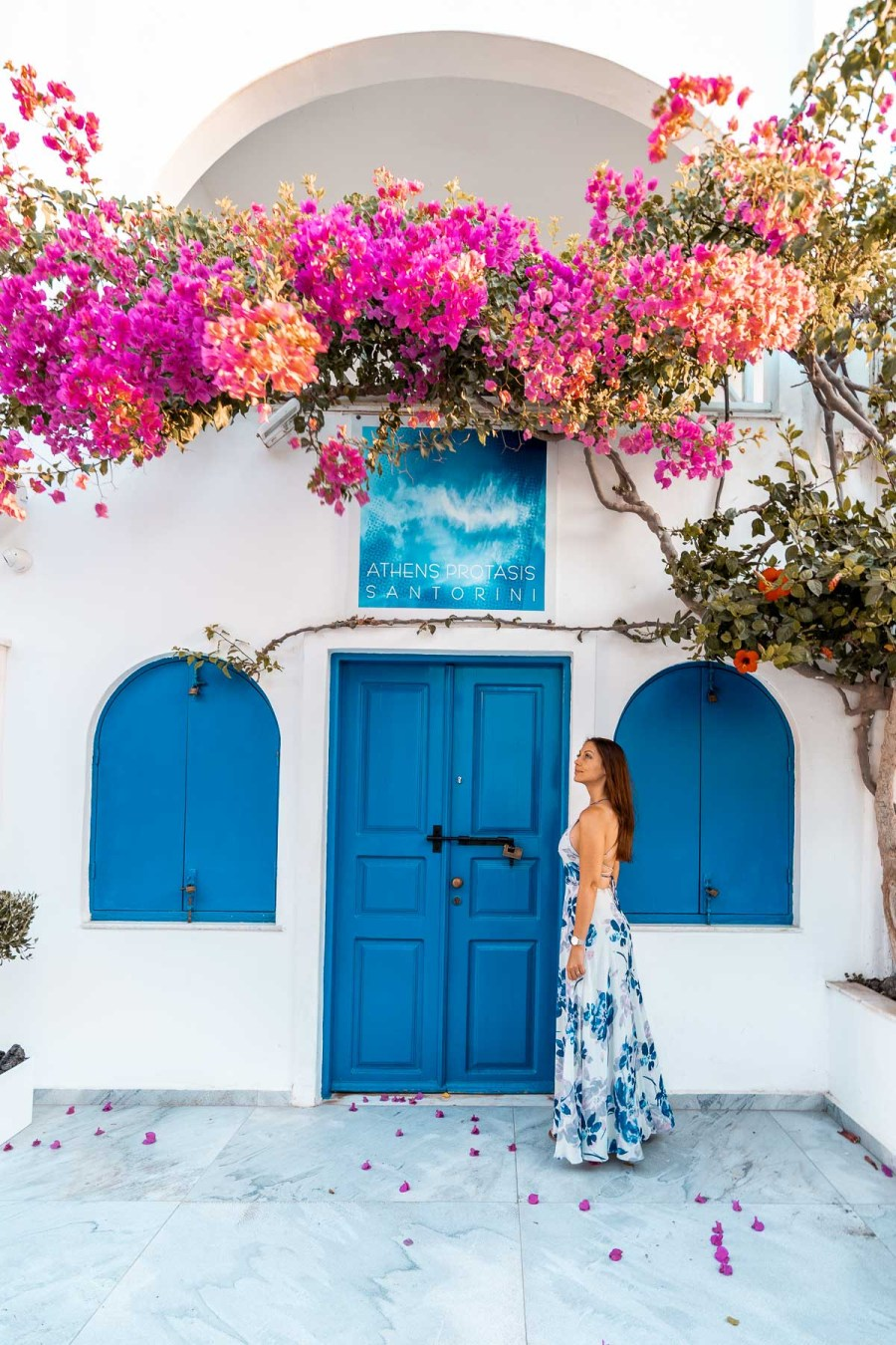 Girl in a blue floral dress standing in front of a blue door with pink flowers in Oia, Santorini