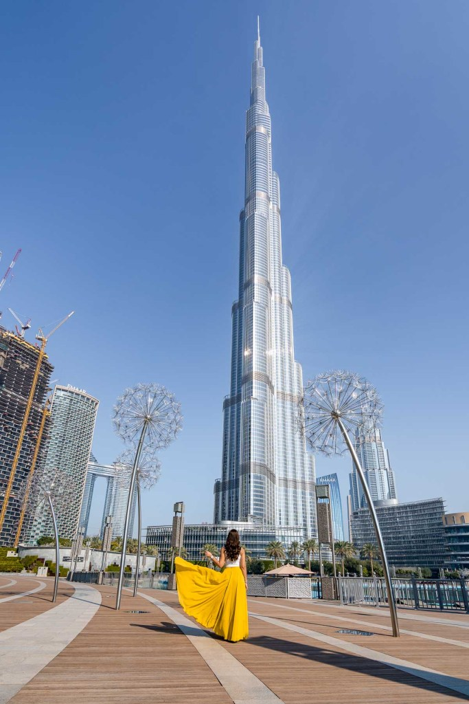 Girl in yellow skirt standing in the Burj Park by Emaar in Dubai with the Burj Khalifa in the background