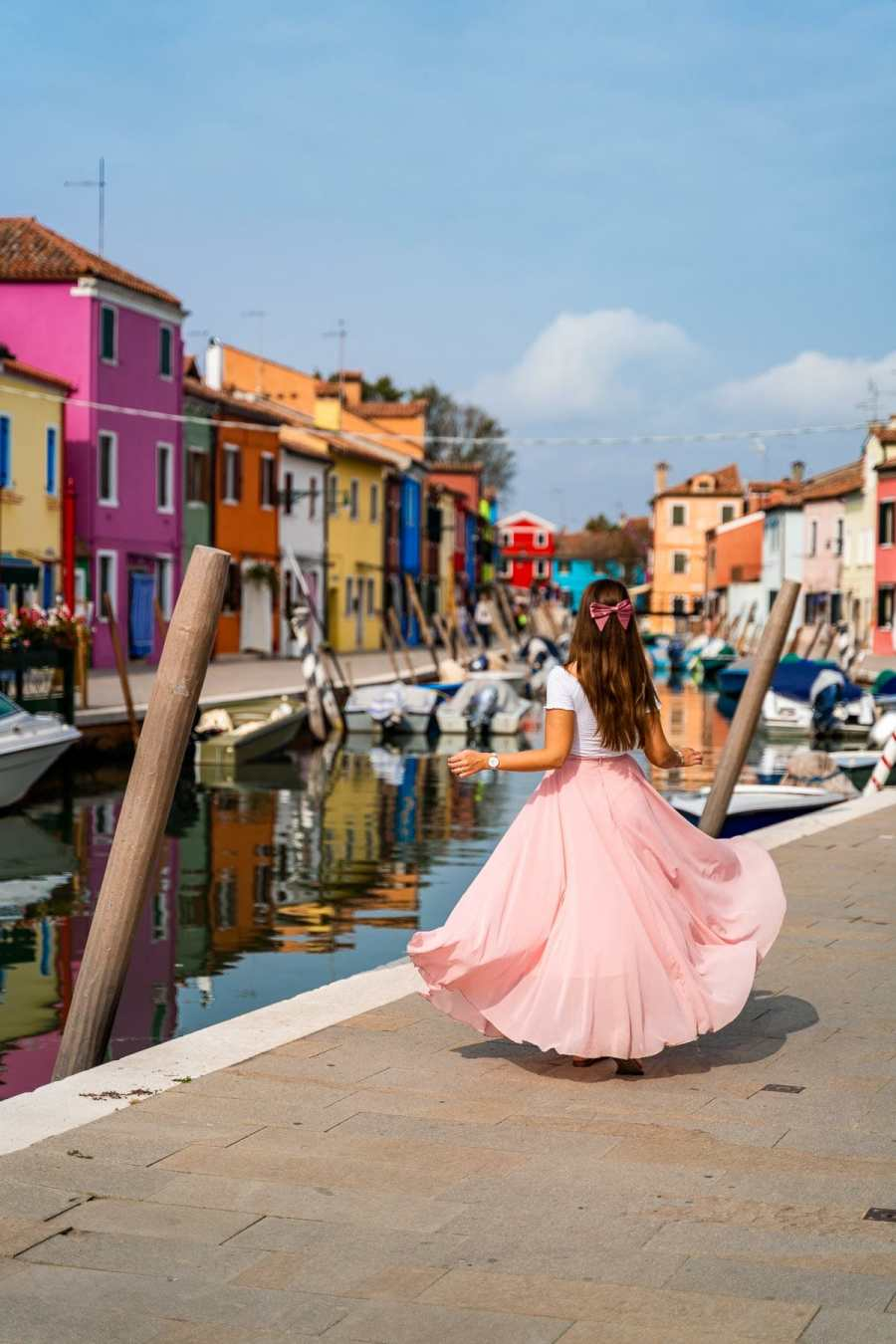 Girl in a pink skirt twirling in front of the colorful houses in Burano