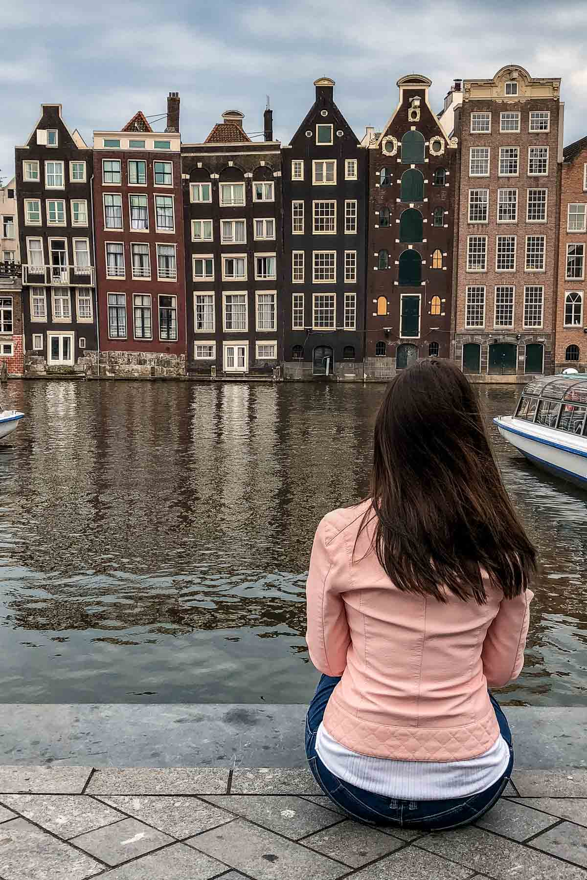 Girl in a pink jacket sitting in front of the crooked houses in Amsterdam
