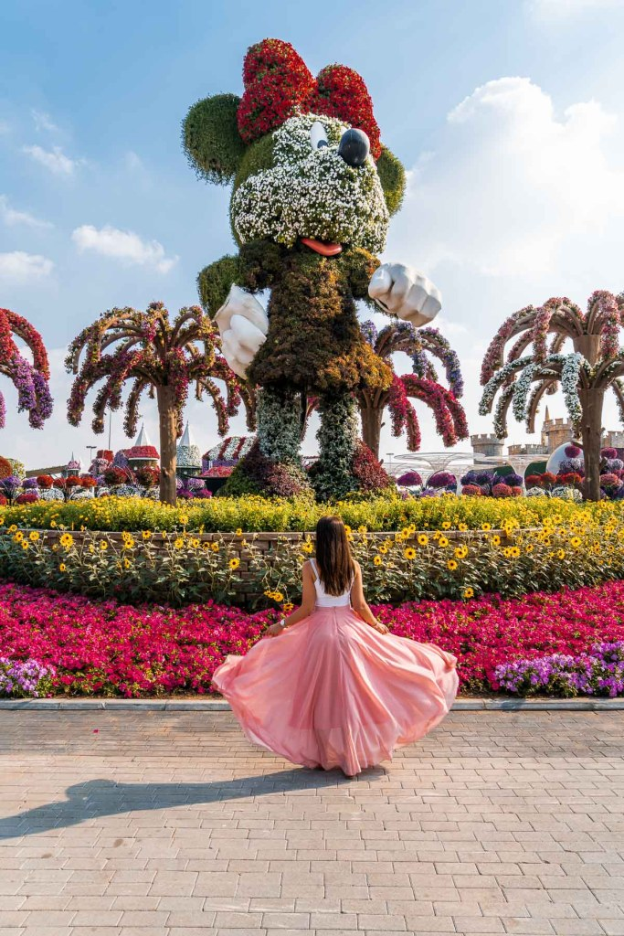 Girl in a pink flowy skirt standing in front of a huge Minnie statue made of flowers in the Dubai Miracle Garden