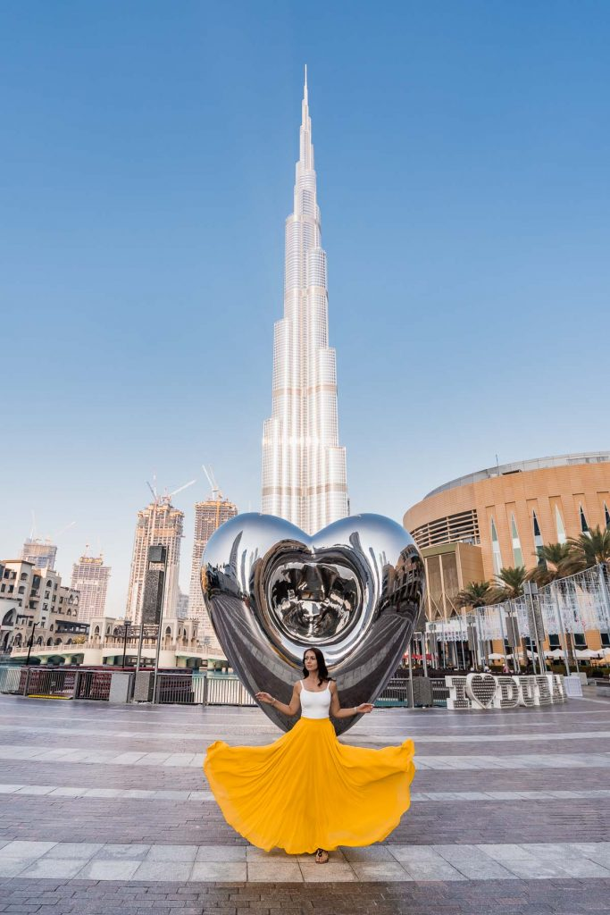 Girl in yellow skirt doing a skirt flip in front of the Dubai Steel Heart with the Burj Khalifa in the background