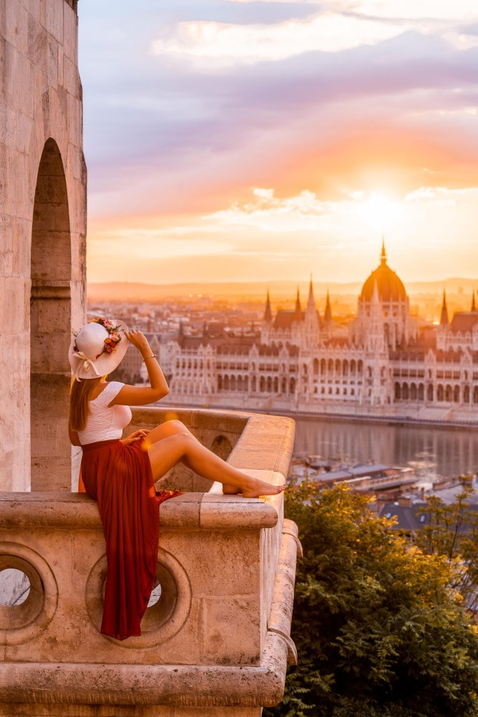 Girl in a red dress sitting on a balcony at the Fisherman's Bastion, looking at the Hungarian Parliament at sunrise
