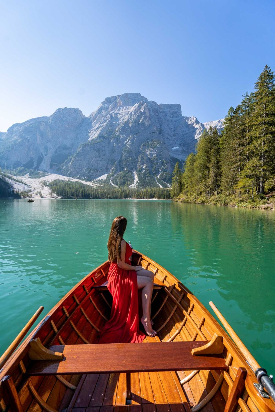 Girl in a red dress sitting in a rowboat at Lago di Braies in the Dolomites