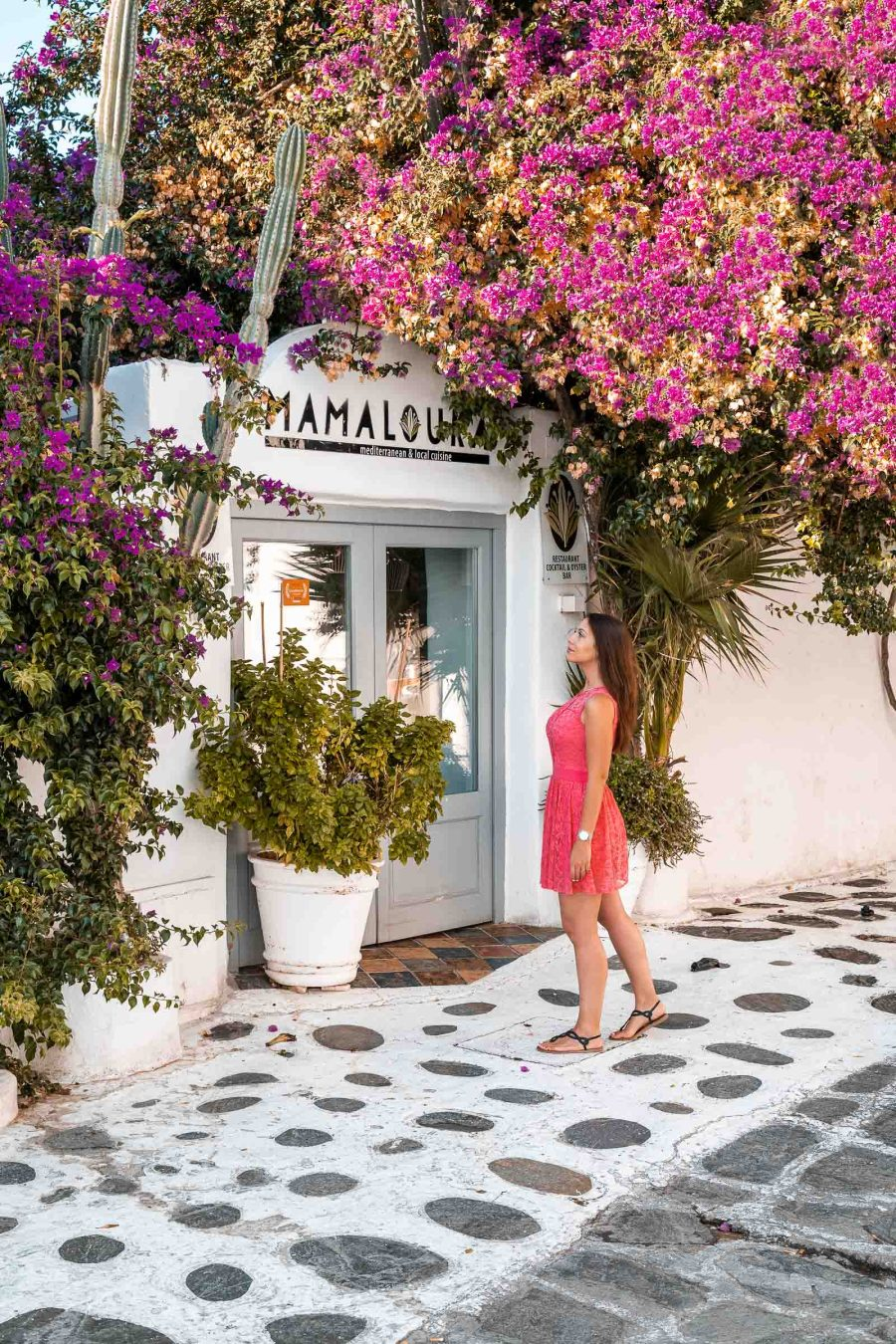 Girl in a pink dress standing in front of Mamalouka Restaurant in Mykonos