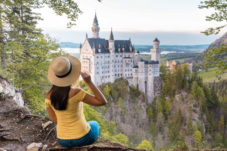 Girl in yellow top and a straw hat sitting at the edge of a cliff, looking at the sunset over the Neuschwanstein Castle