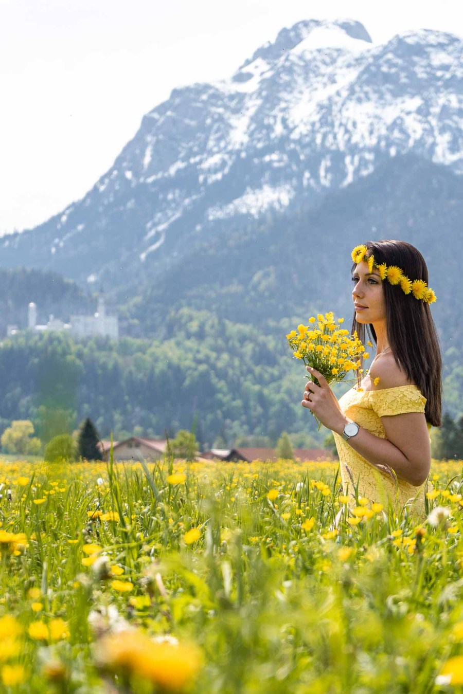 Girl in a flower crown sitting in a daffodil field with the Neuschwanstein Castle in the background