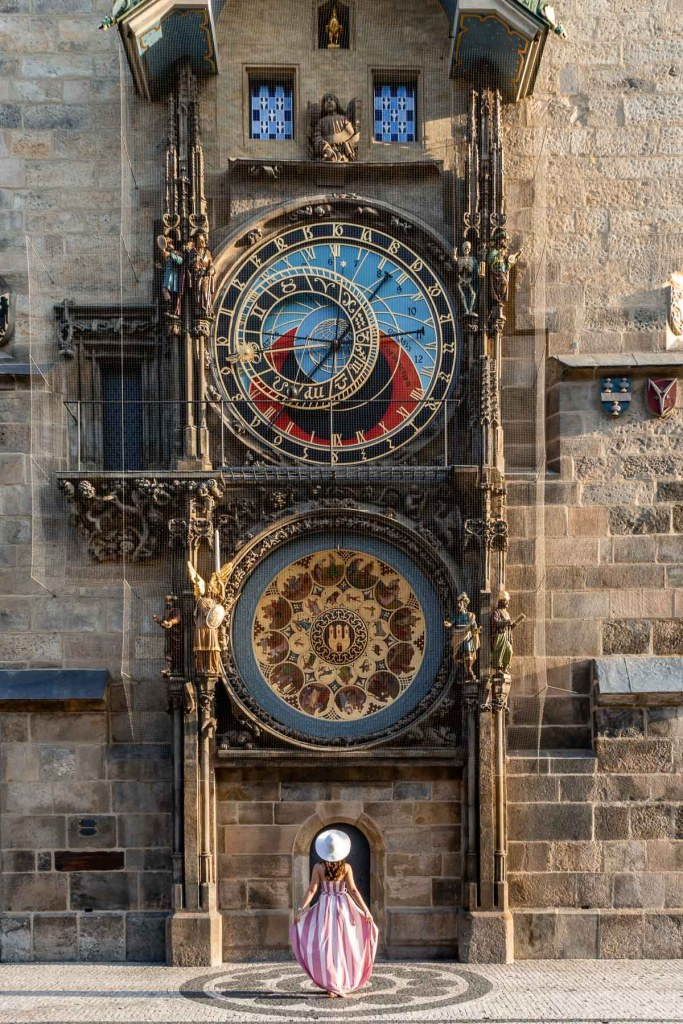 Girl in a pink dress standing in front of the Orloj Astronomical Clock in Prague