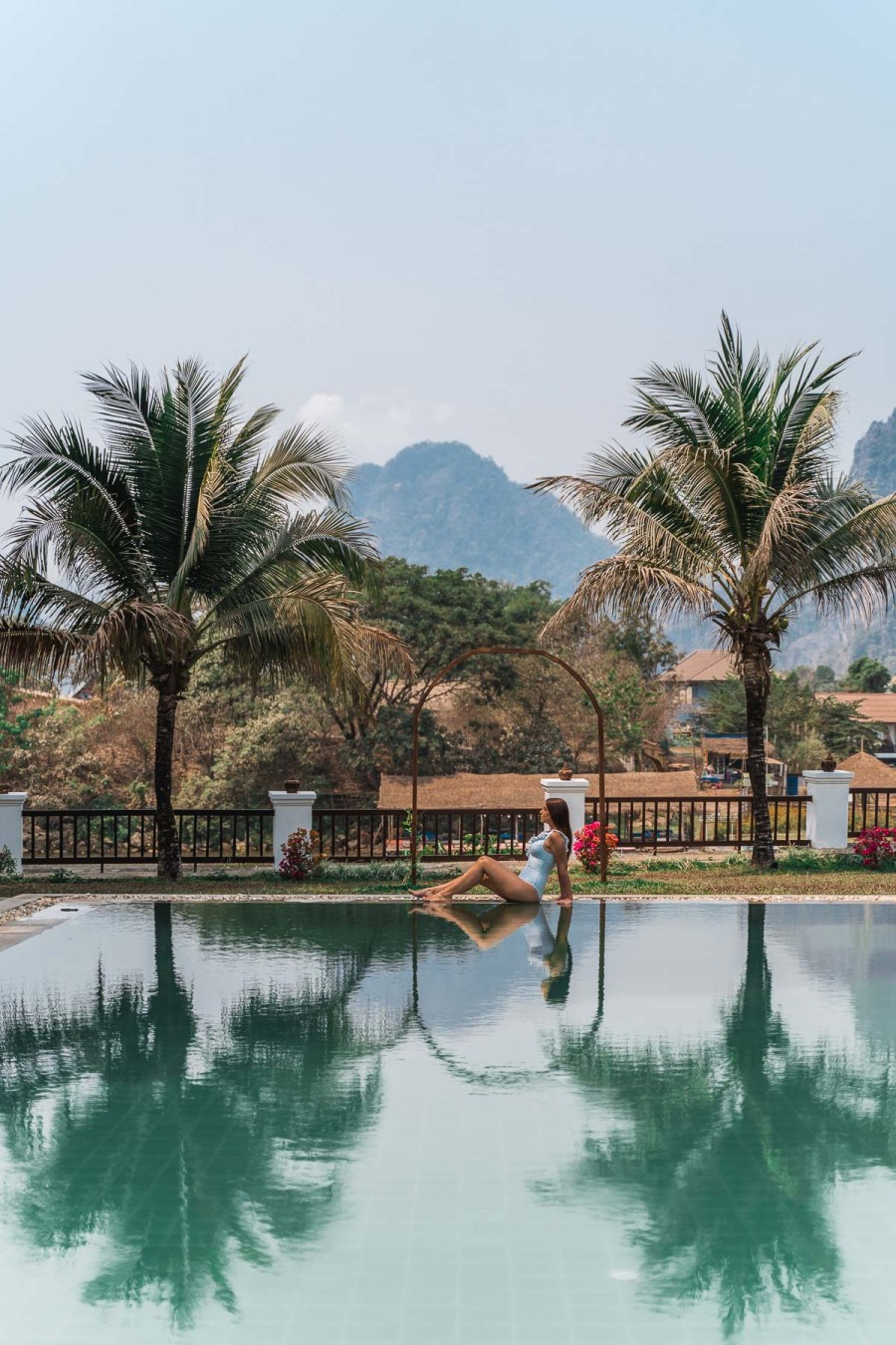 Girl in a blue swimsuit sitting by the pool at the Riverside Boutique Resort Vang Vieng