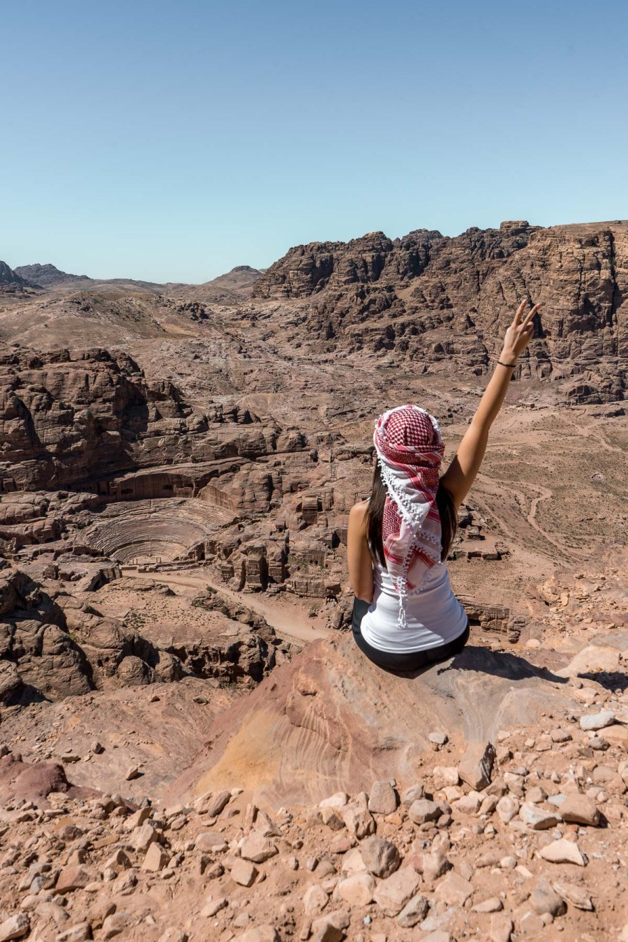 Girl in a white top and a white-red keffiyeh looking at the Nabatean ruins in Petra, Jordan