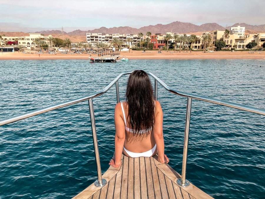 Girl in a white bikini sitting on a snorkeling boat in Aqaba, Jordan
