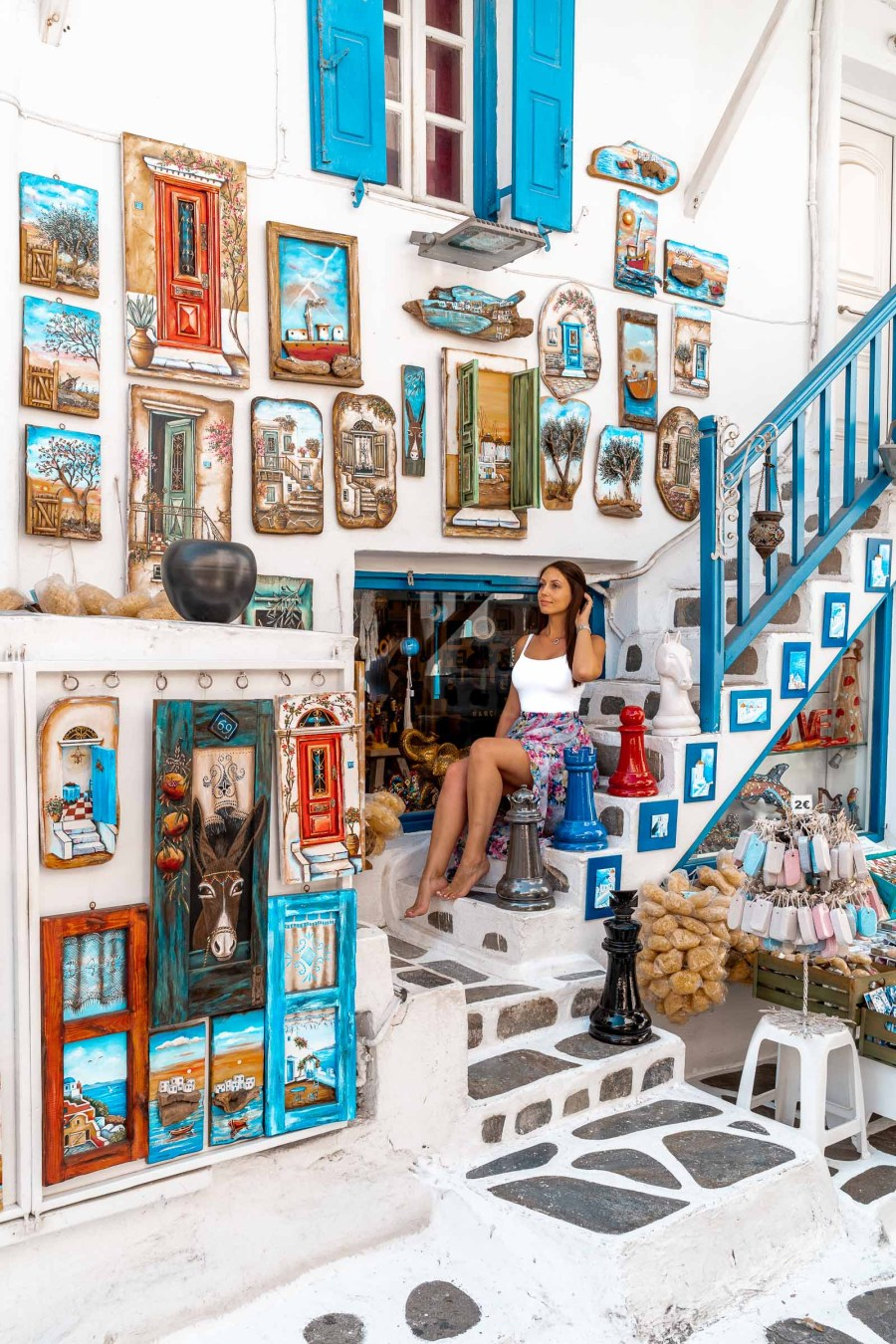Girl sitting on a stairway in front of a cute souvenir shop in Mykonos