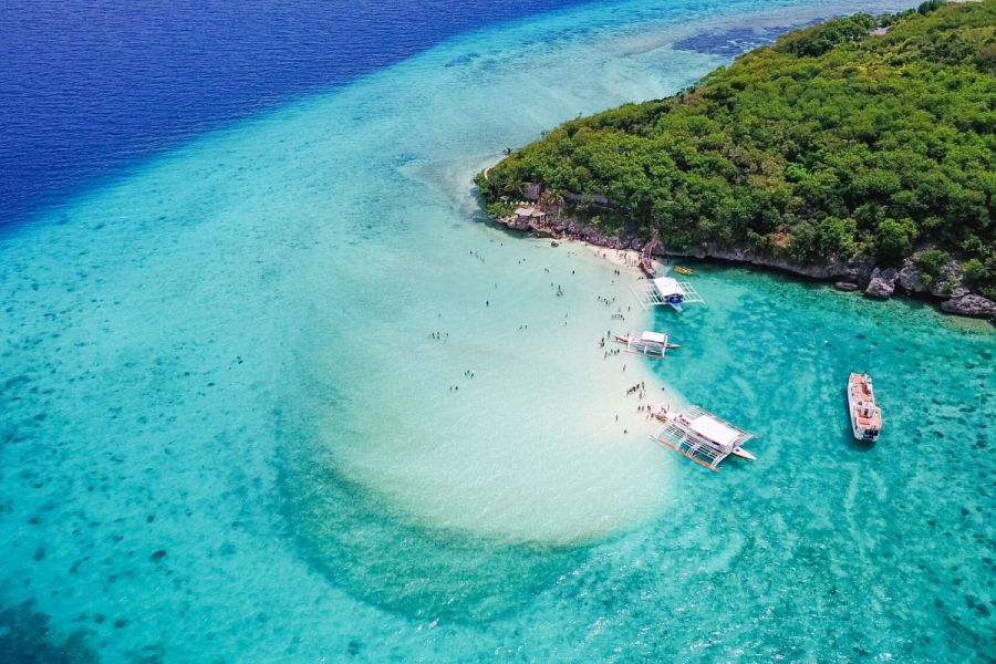 Tourists swimming in the crystal clear blue water at Sumilon Island, Philippines