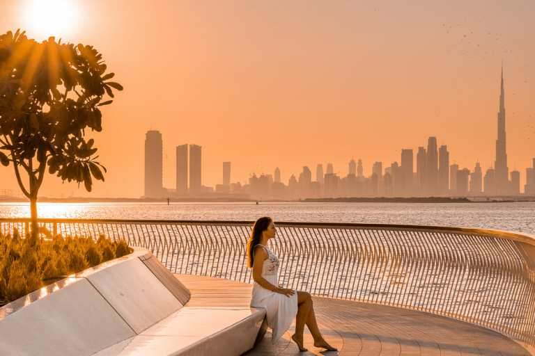 Sunset at Dubai Creek Harbour with girl in a white dress sitting in the middle