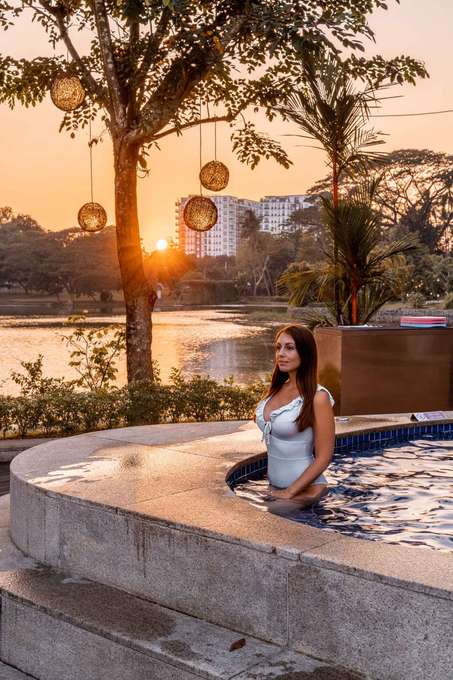 Girl in a blue bathing suit sitting in the hot tub watching the sunset at Lotte Hotel Yangon