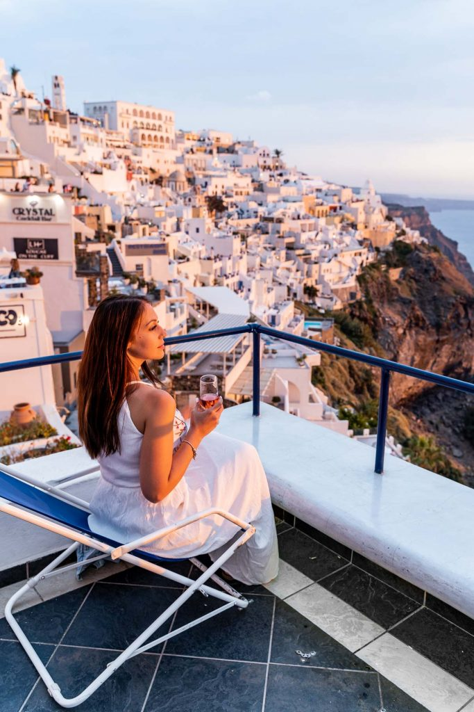 Girl in a white dress watching the sunset at Franco's Bar in Fira, Santorini