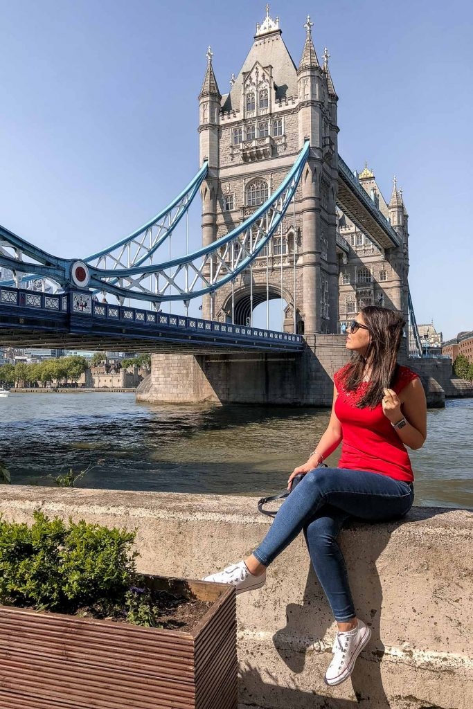 Girl in a red shirt sitting in front of the Tower Bridge in London