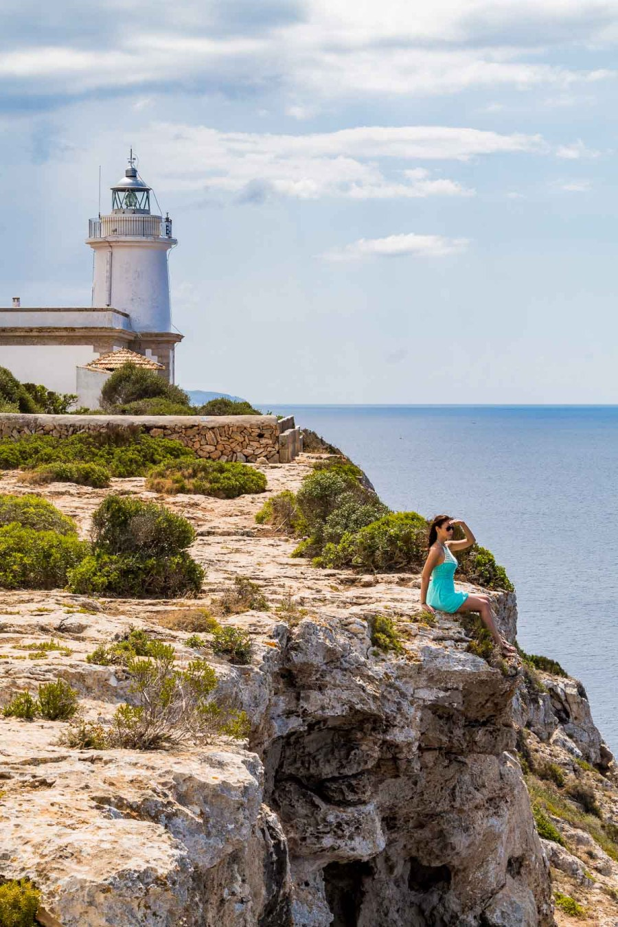 Girl in a blue dress sitting in front of Far de Cap Blanc lighthouse in Mallorca