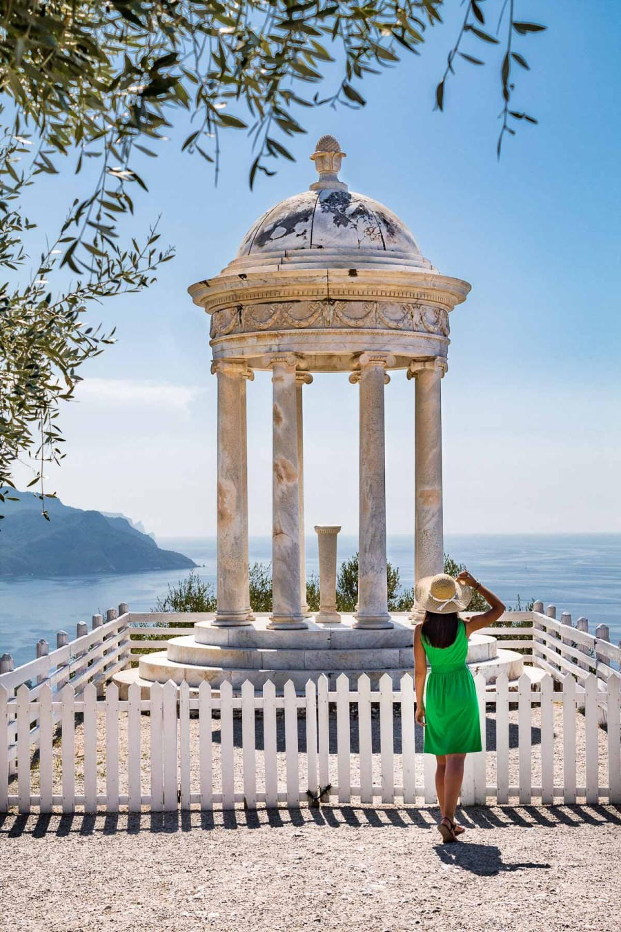Girl in a green dress standing in front of a marble column at Son Marroig, one of the must visit places on every Mallorca road trip