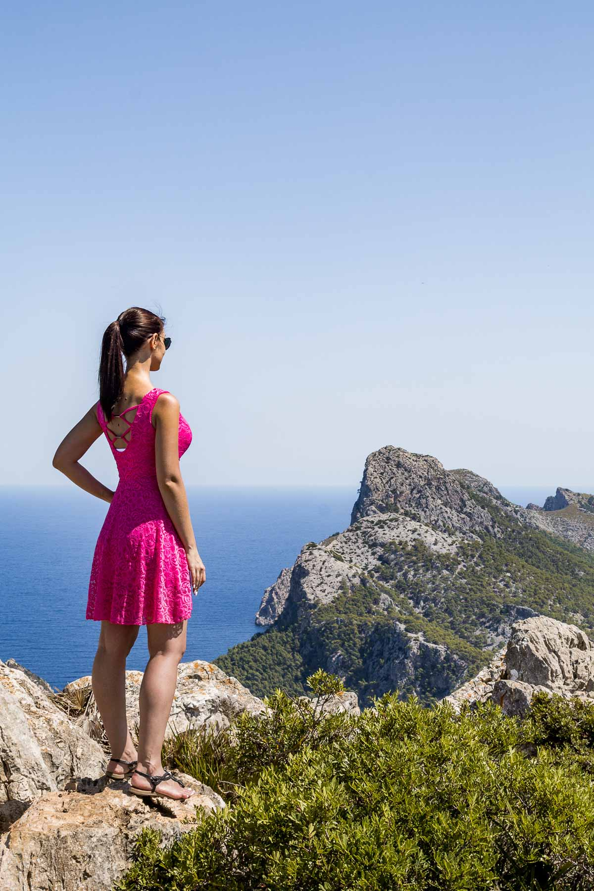 Girl in a pink dress looking at the beautiful view from Albercutx watchtower in Mallorca