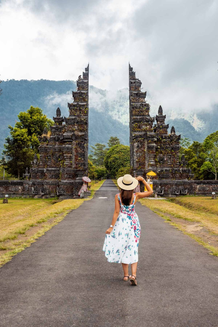 Girl in a floral dress standing in front of the Handara Gate in Bali
