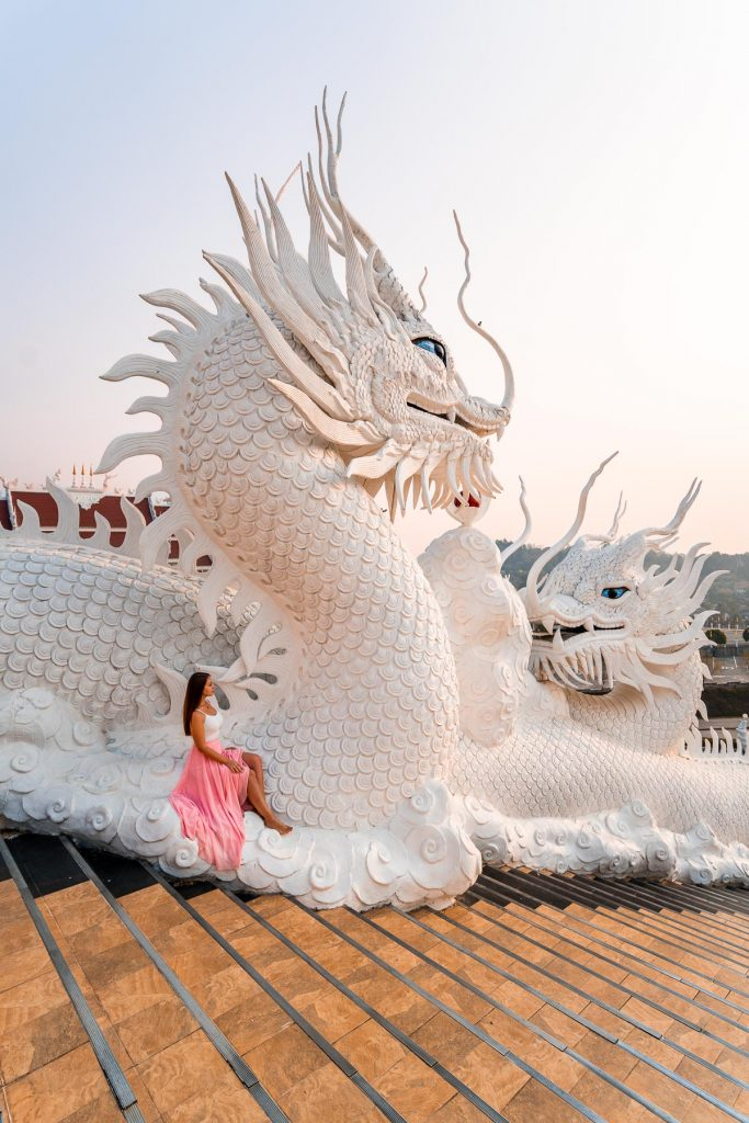Girl in a pink skirt sitting on a dragon statue at Huay Pla Kang Temple in Chiang Rai