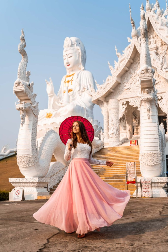 Girl in a pink standing in front of Huay Pla Kang Temple in Chiang Rai
