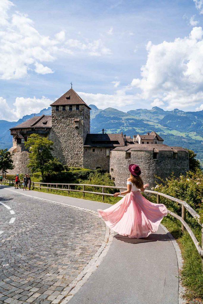 Girl in a pink skirt twirling in front of Vaduz Castle, Liechtenstein