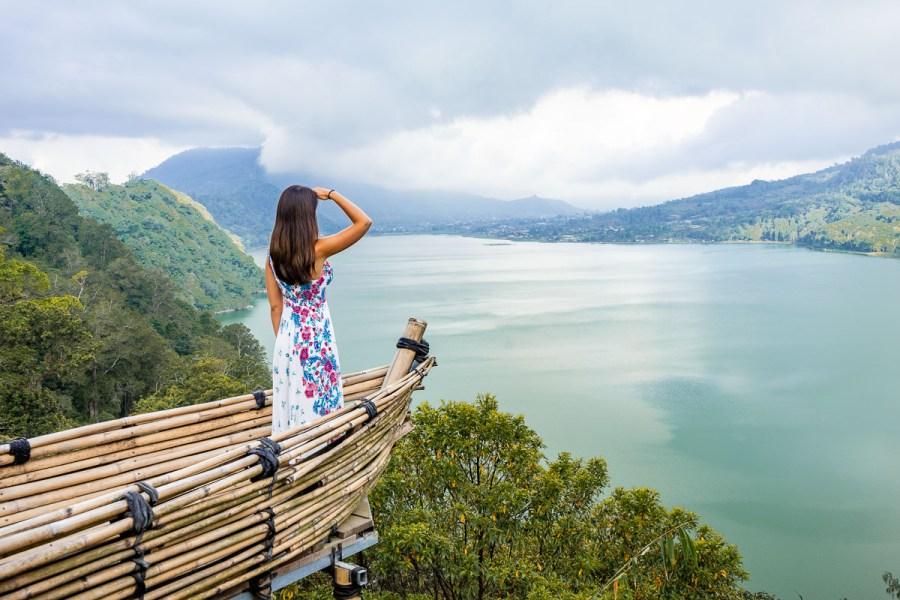 Girl standing in front of a wooden boat at Wanagiri Hidden Hills in Bali