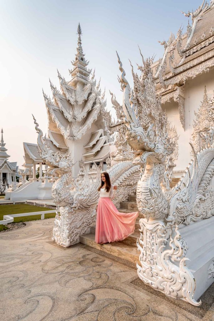 Girl in a pink skirt standing on the stairs in front of Wat Rong Khun, the White Temple in Chiang Rai