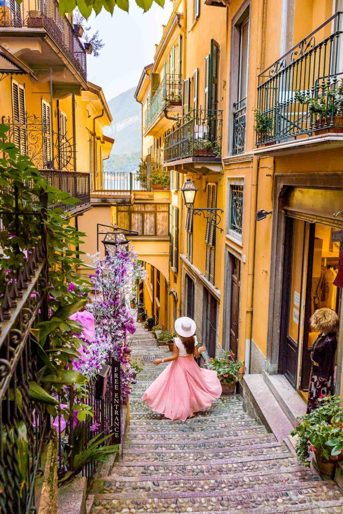 Girl in a pink skirt twirling on a colorful street in Bellagio, Lake Como