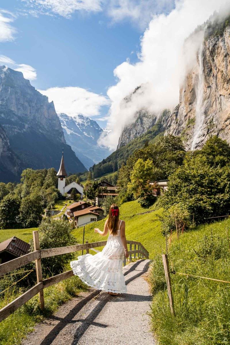Girl in a white dress twirling in the fairytale town of Lauterbrunnen in Switzerland