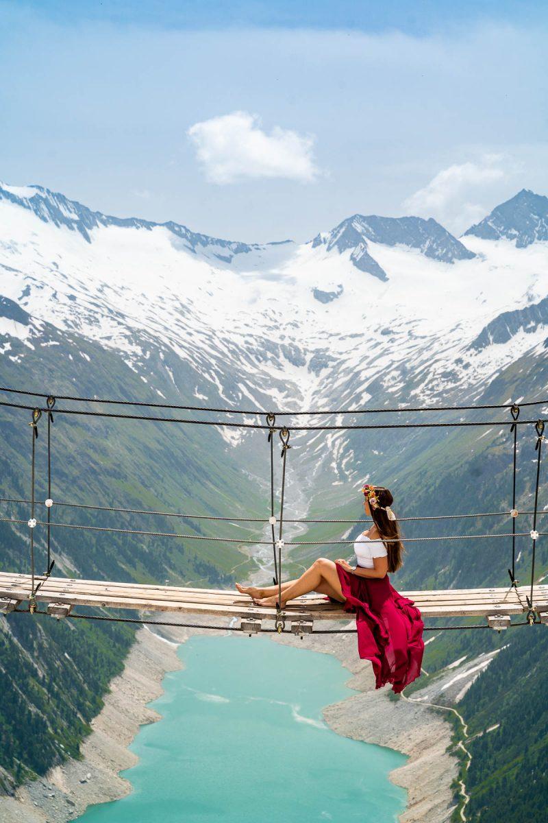 Girl in a red skirt sitting on Panoramabrücke Olpererhütte, Austria