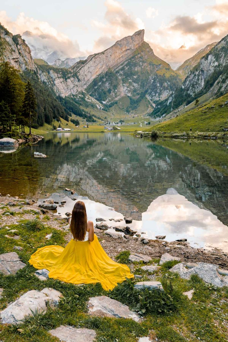 Girl in a yellow dress sitting by Seealpsee, Switzerland
