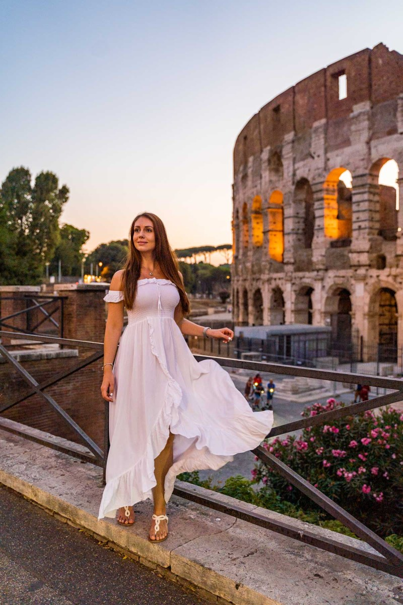 Girl in a white dress in front of the Colosseum at sunset