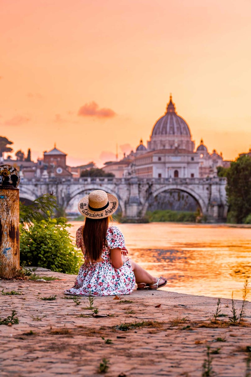 Girl sitting on the shores of River Tiber, watching the sunset in Rome, Italy