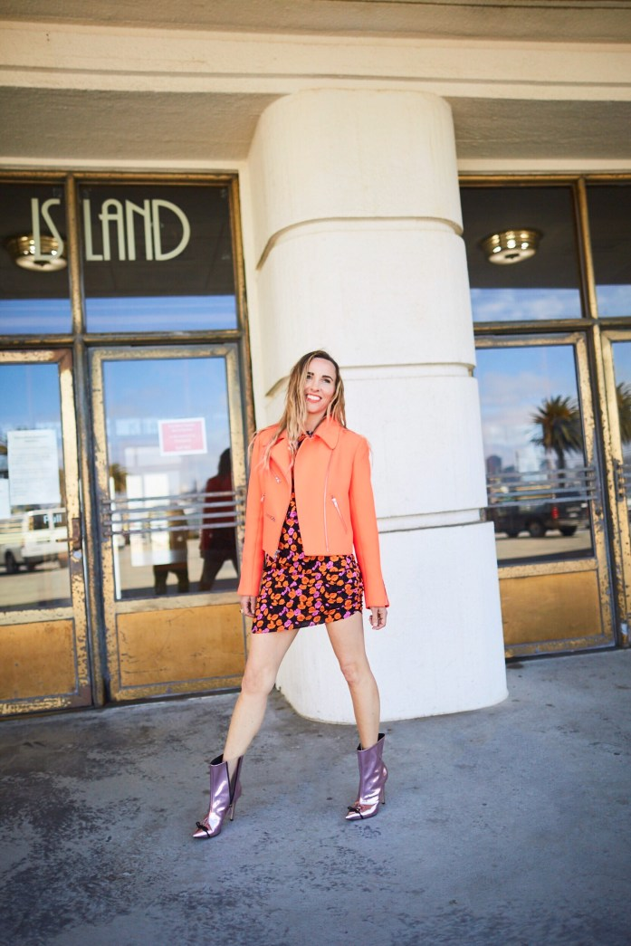 ALC neon motorcycle jacket with floral print dress and metallic pink boots.